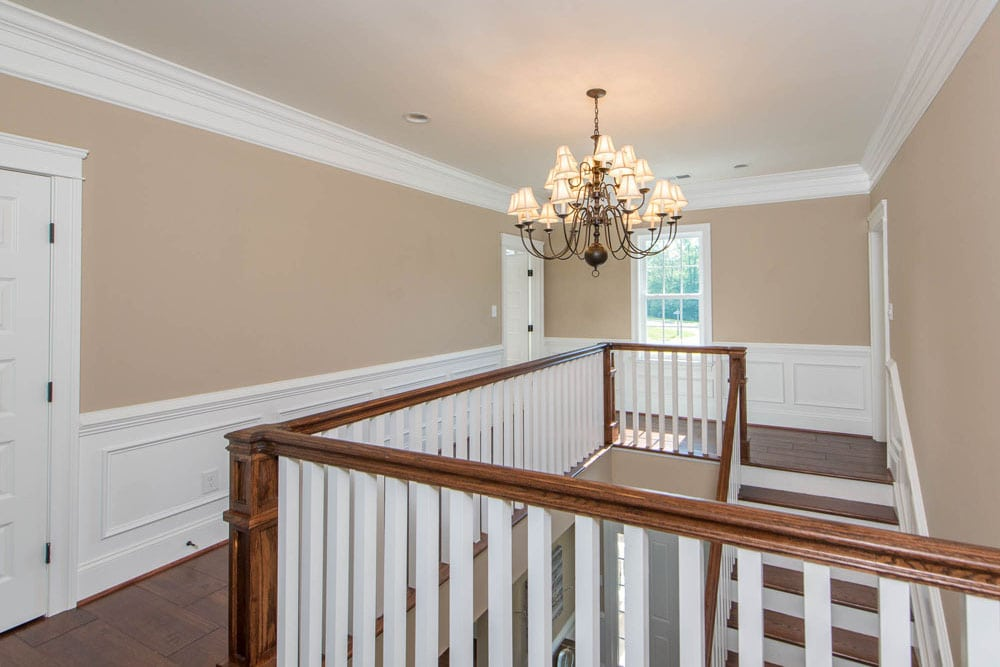 Second floor stair and hallway with large chandeliers in Fairfax home