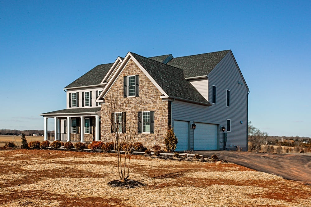 Side of brown stone and white slat Leesburg home with driveway and garage