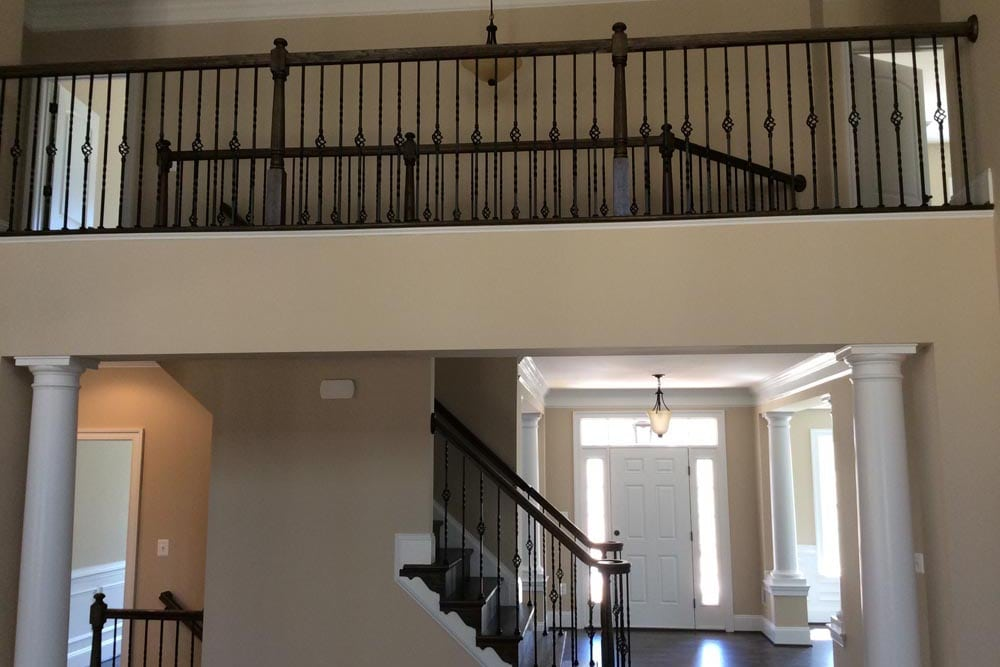 Side view of Round Hill home interior stairs and second floor hallway with railing