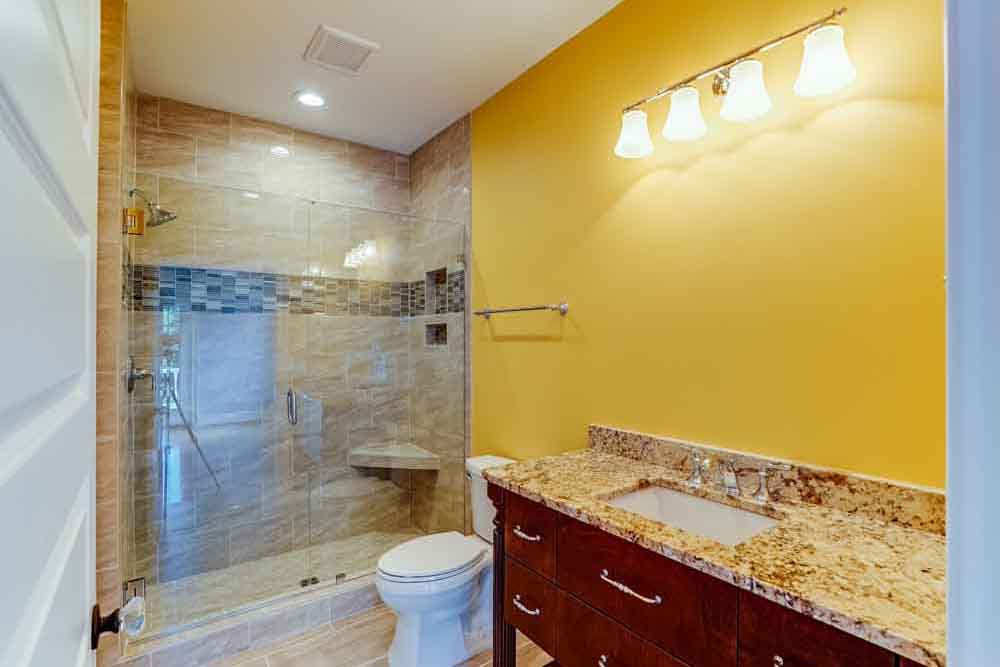 Small bathroom with granite shower and sink countertop and then a toilet in Middleburg home