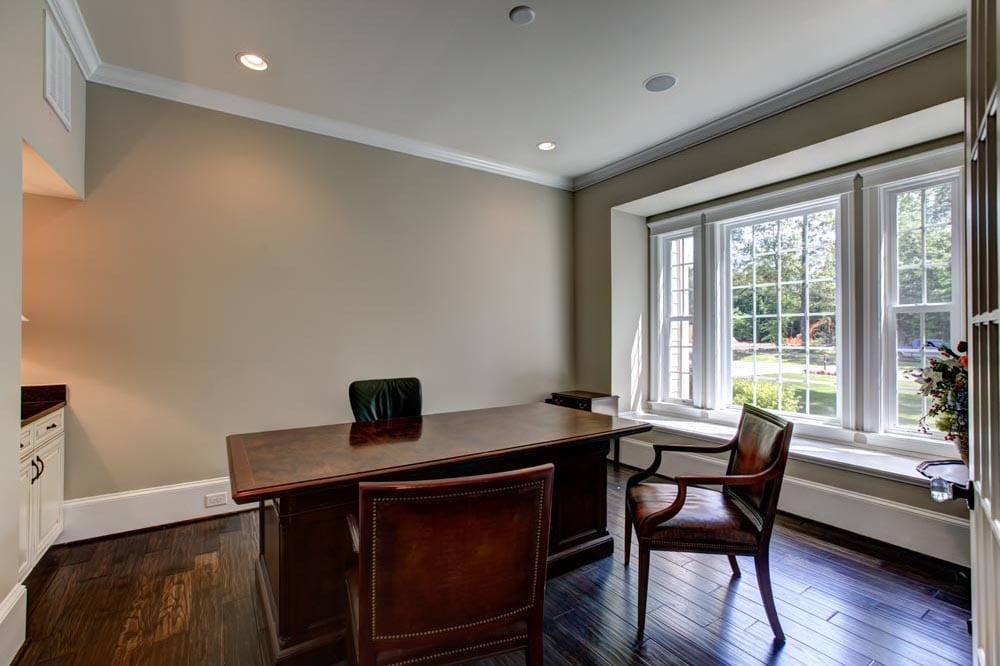 Small office area with chairs, desk, and window