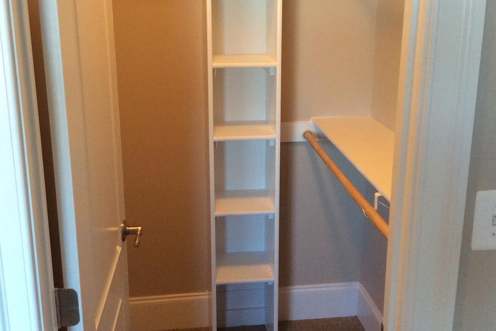 Small walkin closet with shelves, places for hanging clothes, and tall shoe rack