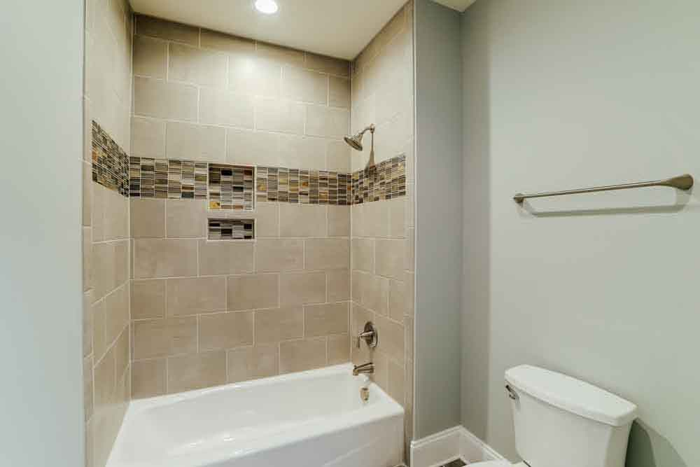 Smaller bathroom with grey tiled shower in Middleburg guestroom