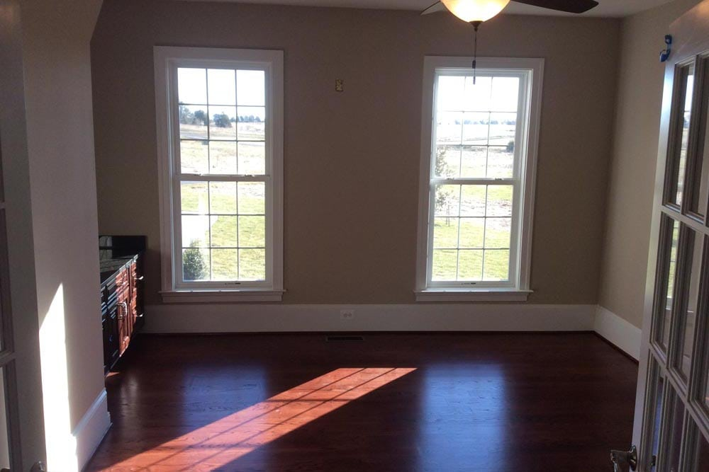 Smaller room in a house on The Plains with ceiling fan and dark brown wood cabinets and windows
