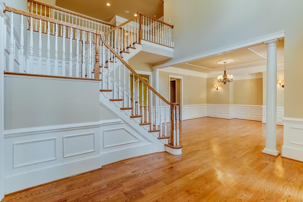 Stairs with landing leading to second story of Middleburg home with chandelier and light brown stained wood floors