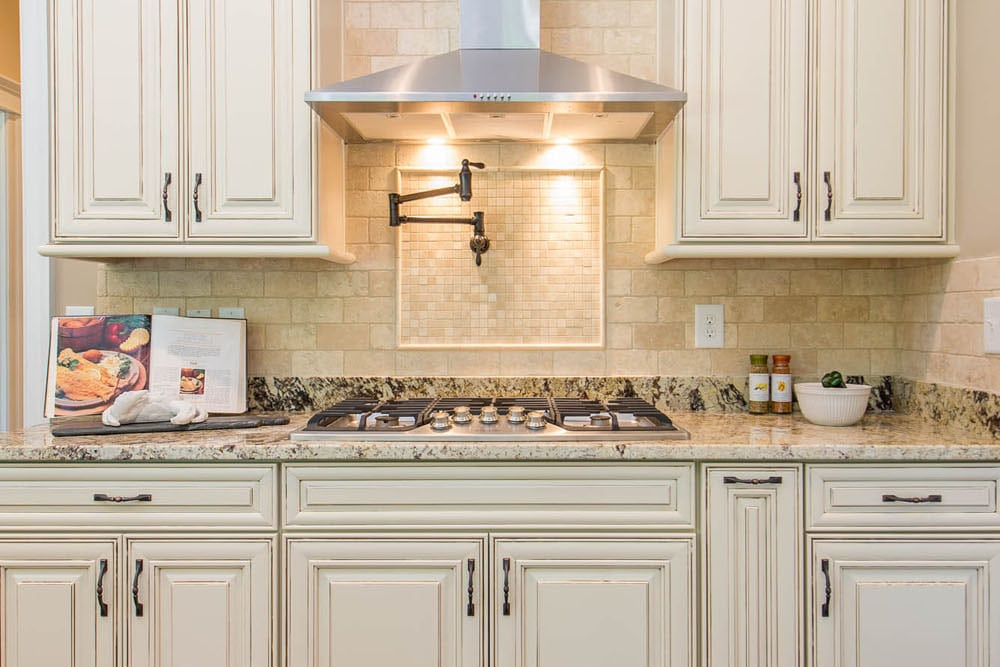 Stove with hood and white cabinets