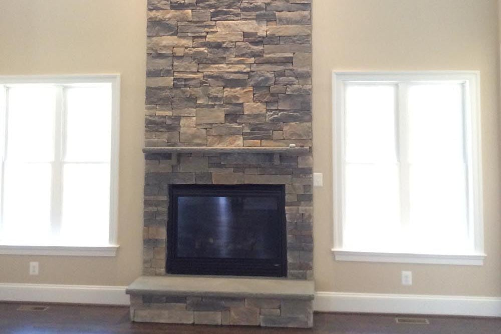 Tall room in Round Hill home with stone fireplace and windows
