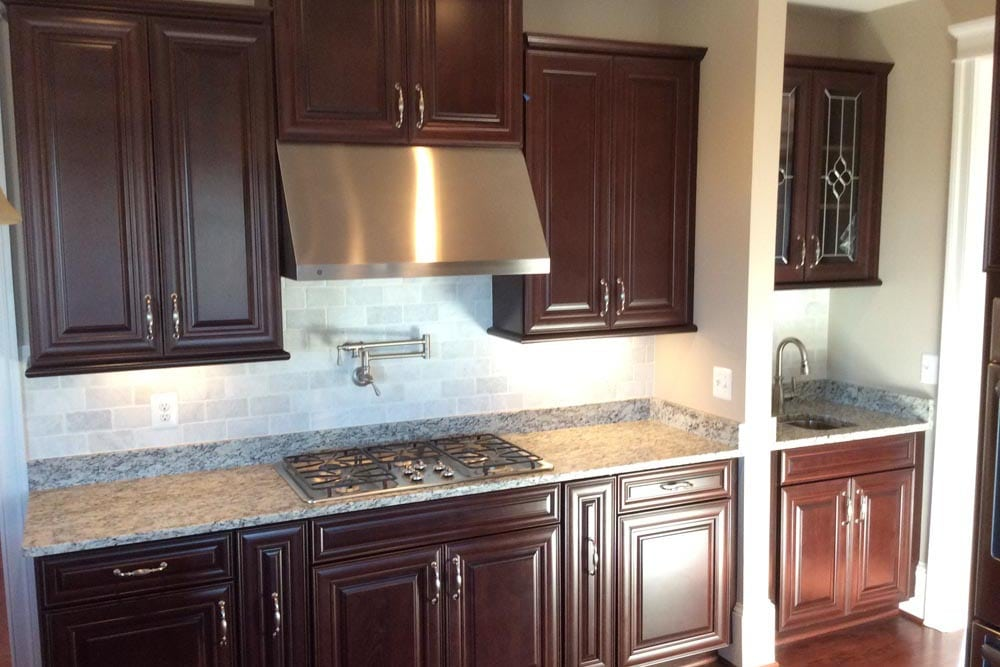 The Plains house kitchen stove with brown cabinets and hood