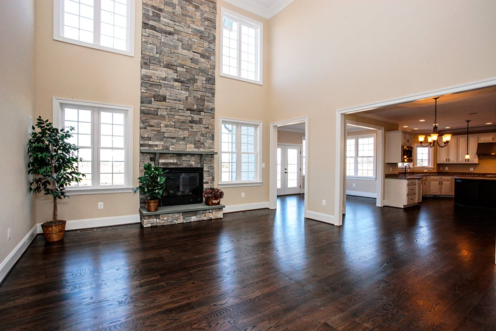 Two story den in Leesburg home with stone fireplace and many windows