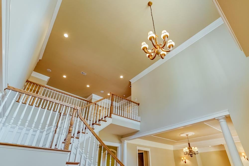 Upward view of stairs and chandelier in Middleburg home
