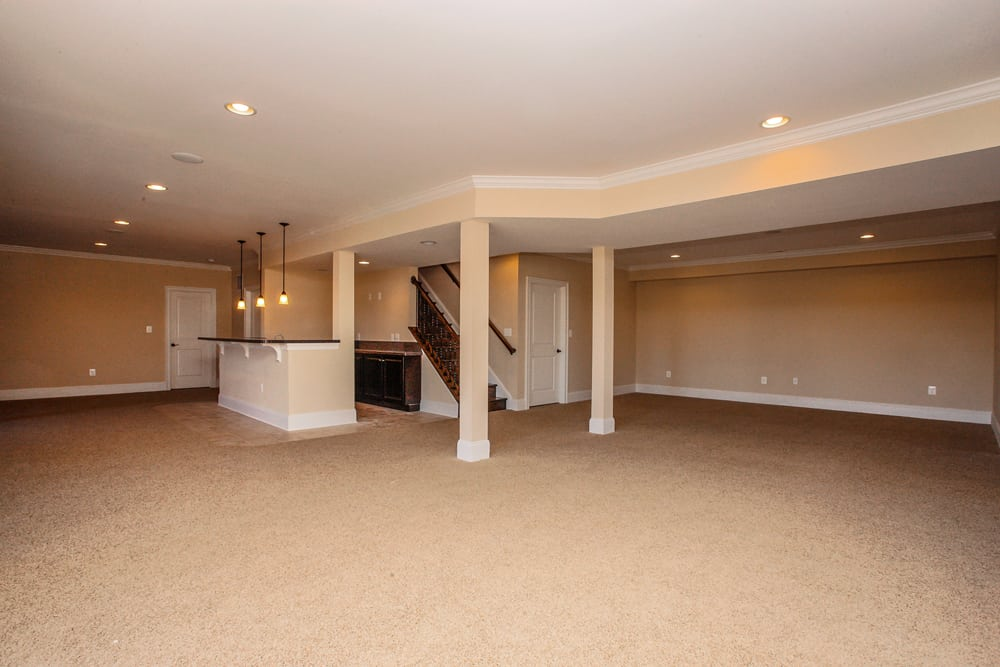 View from glass paneled door of house in Leesburg VA basement with hanging lights over bar