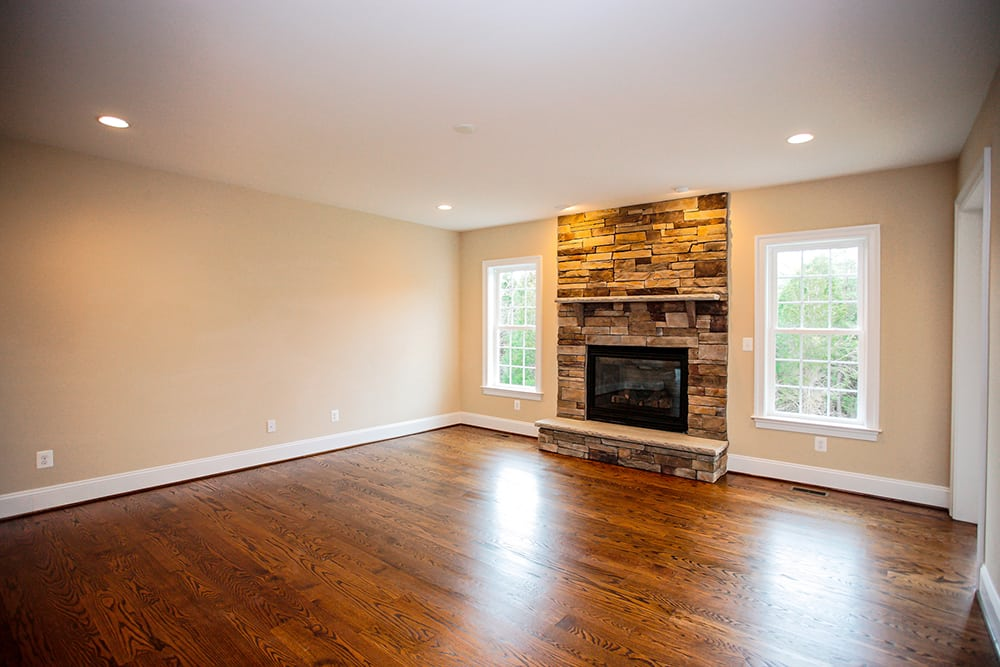View from kitchen into living room with stone fireplace in Warrenton house