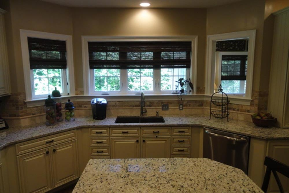 View of Midlands home kitchen from island facing granite countertop sink under window with white cabinets