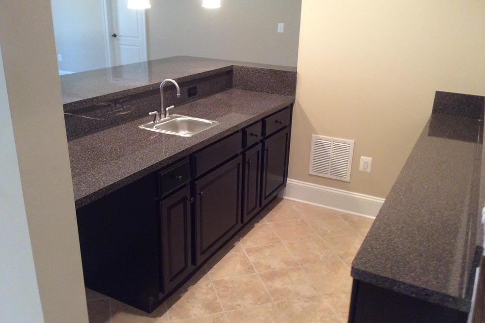 View of behind the bar with a sink and dark brown wood cabinets in Round Hill home