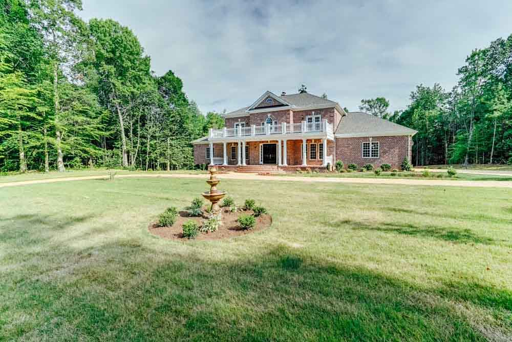 View of brick Middleburg home and front yard fountain
