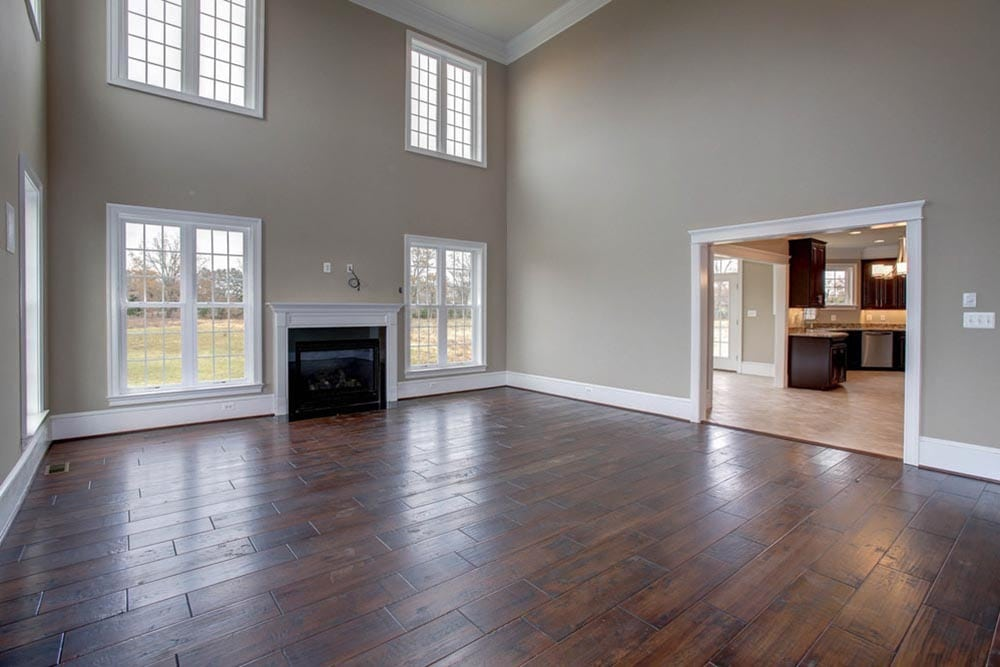 View of den in Culpeper home with stone fireplace and many windows with kitchen in other room