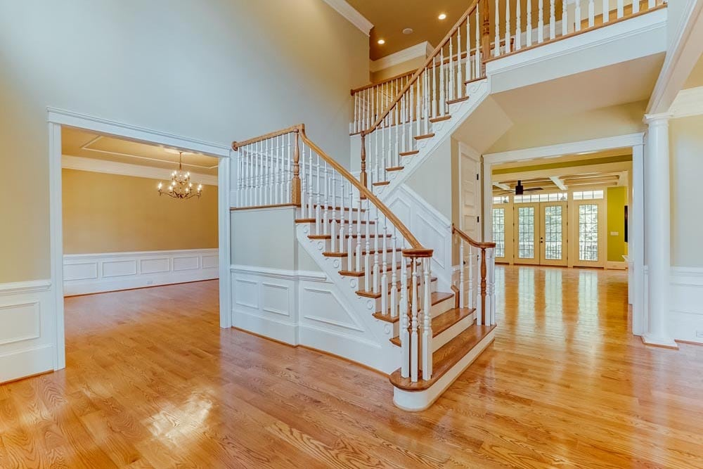 View of front stairs, adjacent room, and hallway leading to kitchen in McLean home