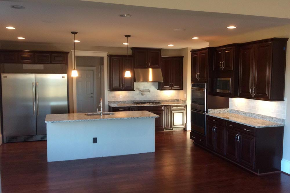 View of kitchen with island and hanging lights and brown cabinets