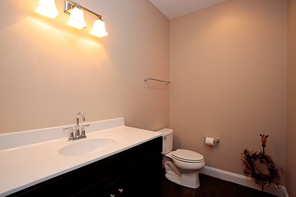 View of large, light pink walled bathroom in Nokesville home with white countertop sink over dark stained cabinets