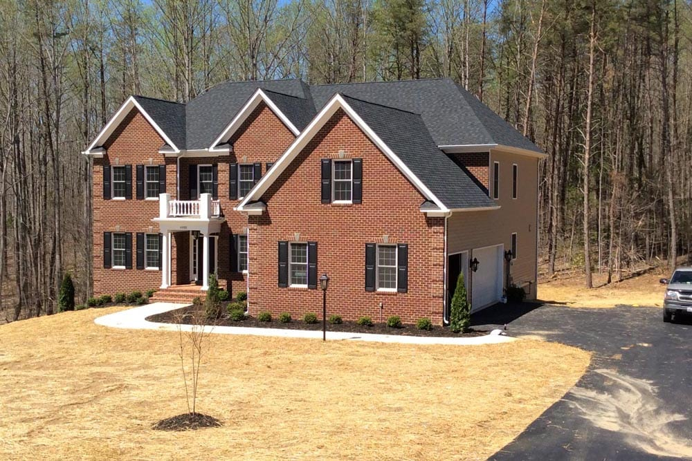 View of red brick Round Hill home with driveway, garage, and truck
