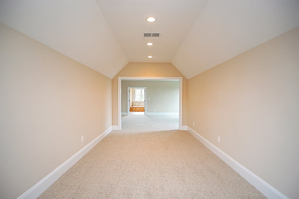 View of upstairs lobby and hallway from carpeted room with angled ceiling
