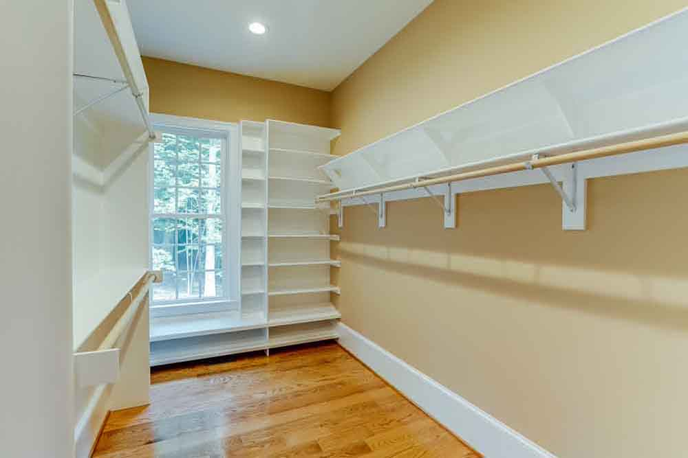 Walkin master bedroom closet in Middleburg home with shelves, hanging space, and a window