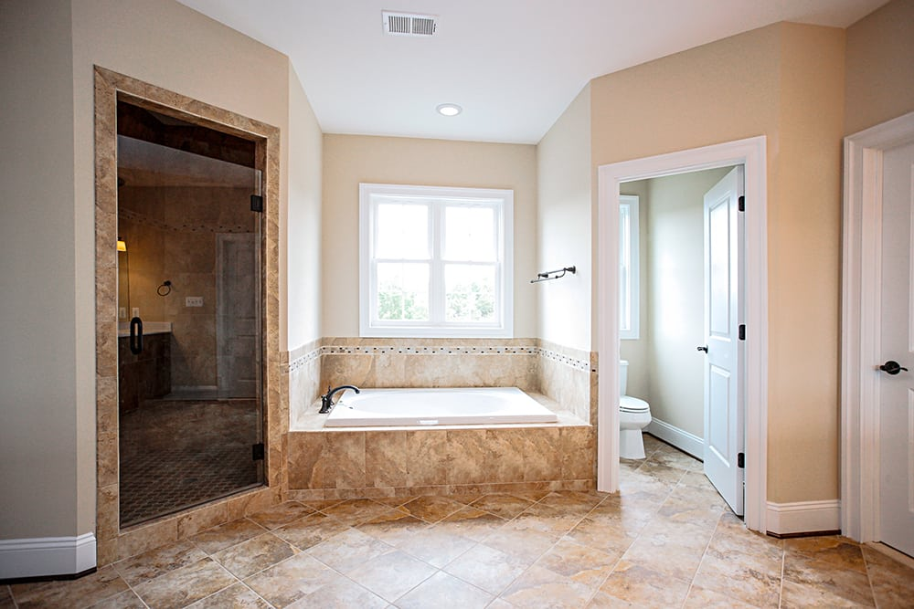 Warrenton house master bathroom with toilet room, bathtub main area, and shower area