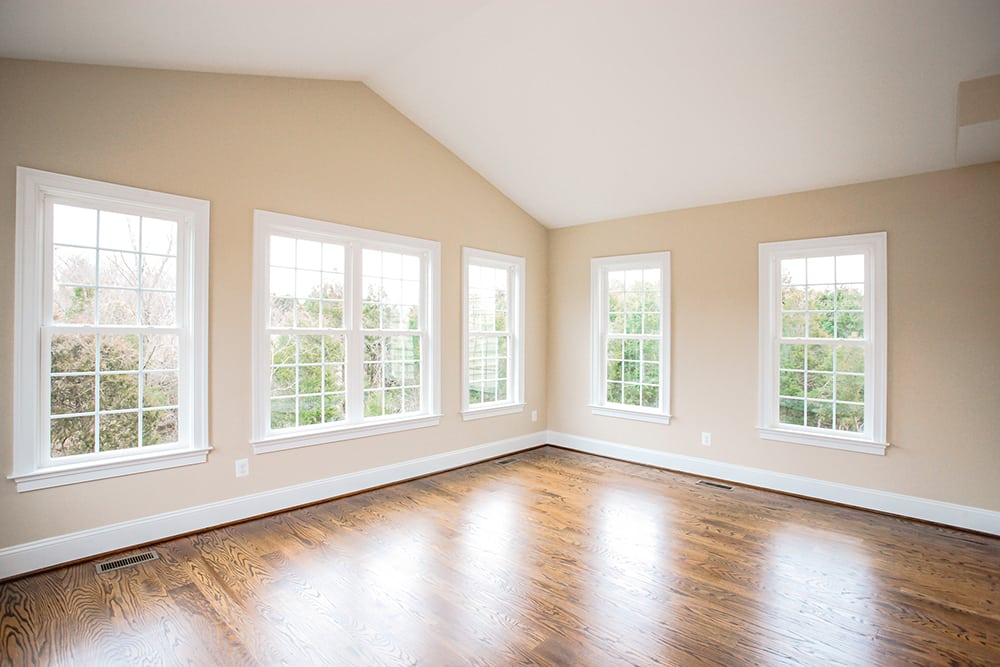 Warrenton room with many windows and stained wooden floor