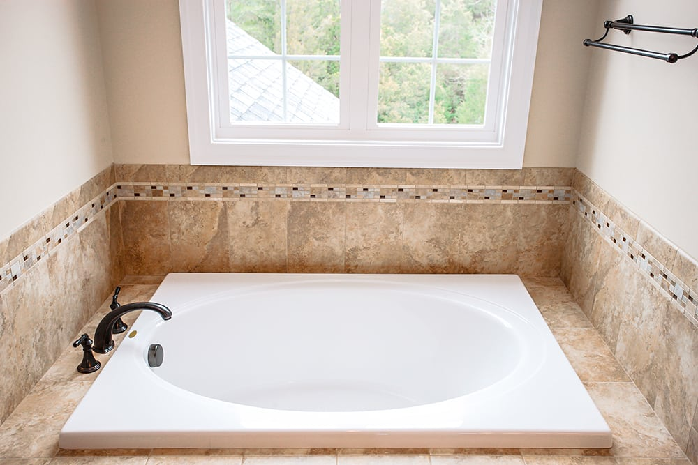 White bathtub with brown surrounding underneath window in master bathroom of Warrenton house