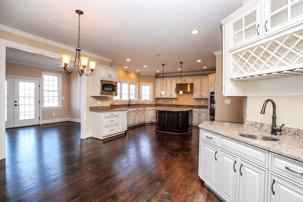 White cabinet and granite countertop kitchen with hanging lights and kitchen island in Leesburg home