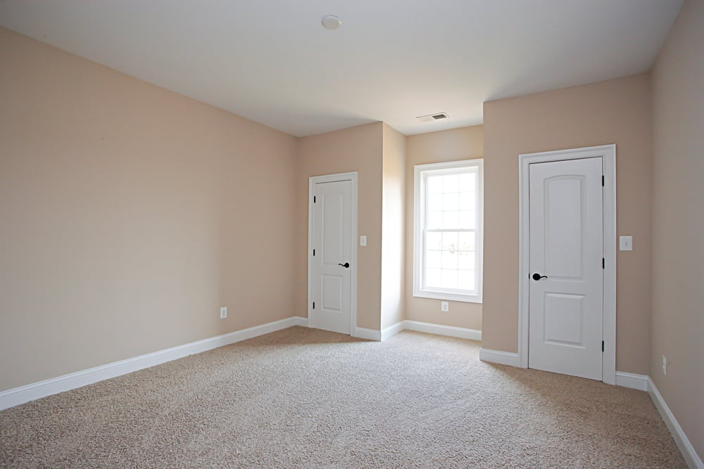 White carpet room in Nokesville home with two doors separated by window