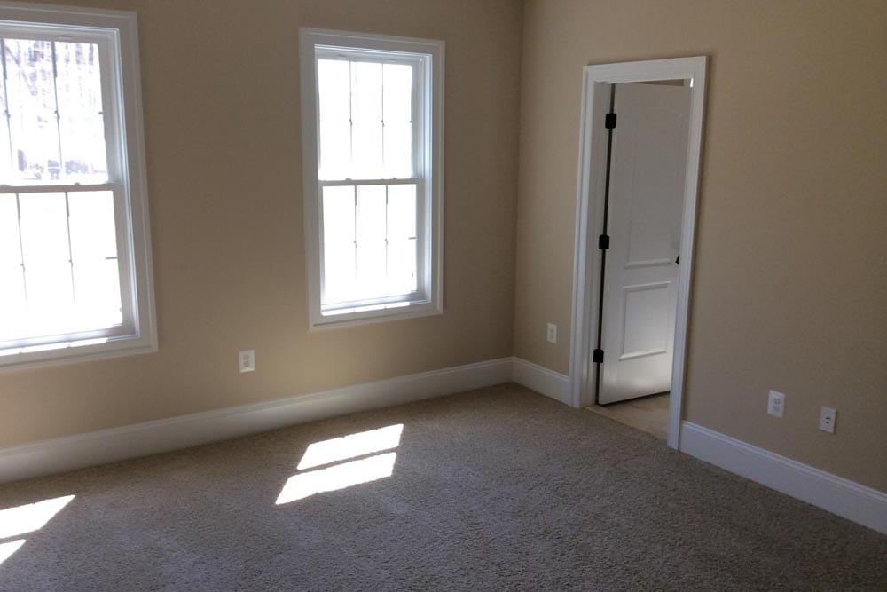 White carpet room in Round Hill home with closet and two windows