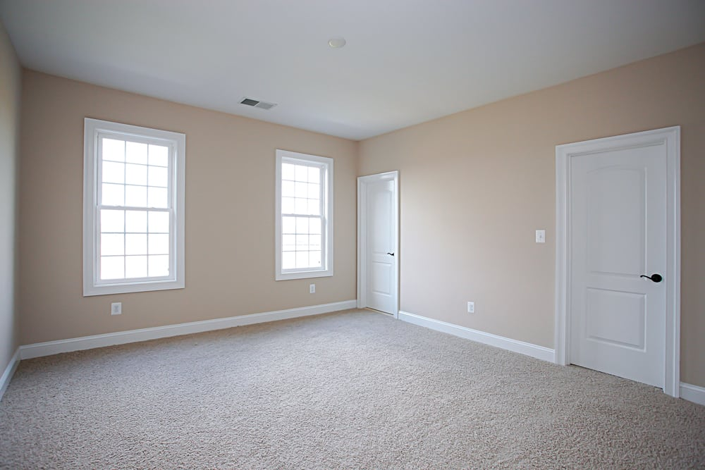 White carpet room inside Nokesville home with two doors