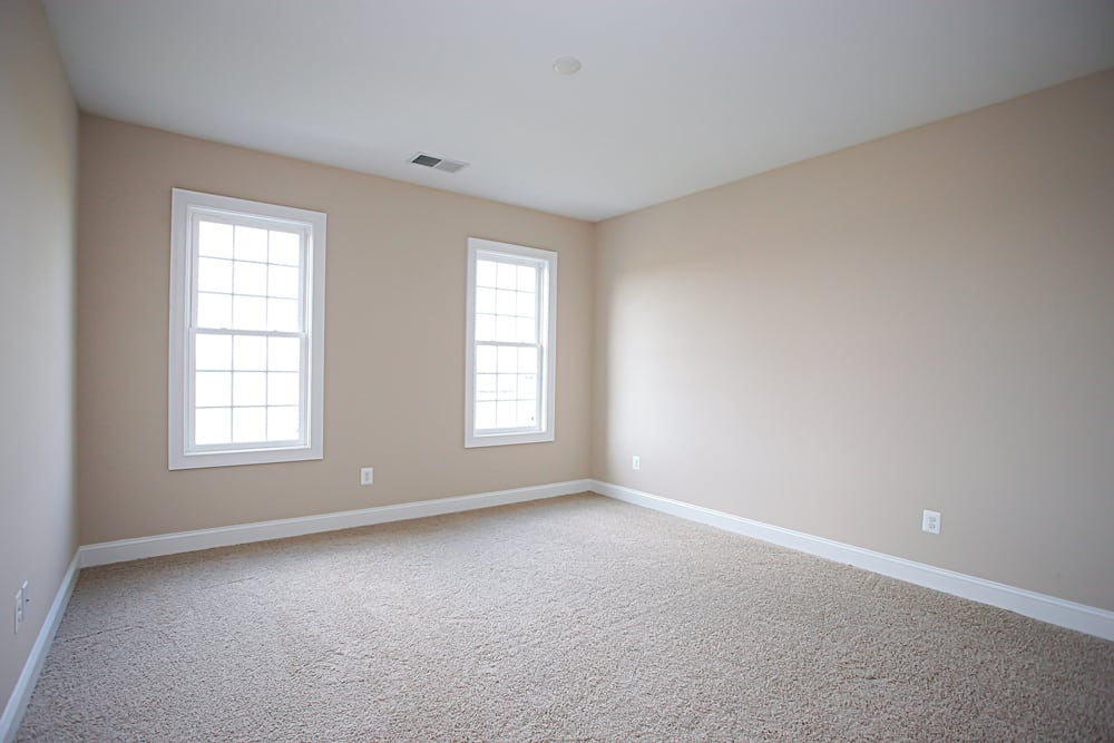 White carpet room with two windows in Nokesville home