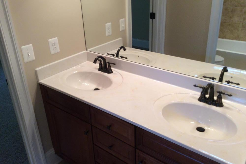 White countertop double sink bathroom with mirror in Round Hill home