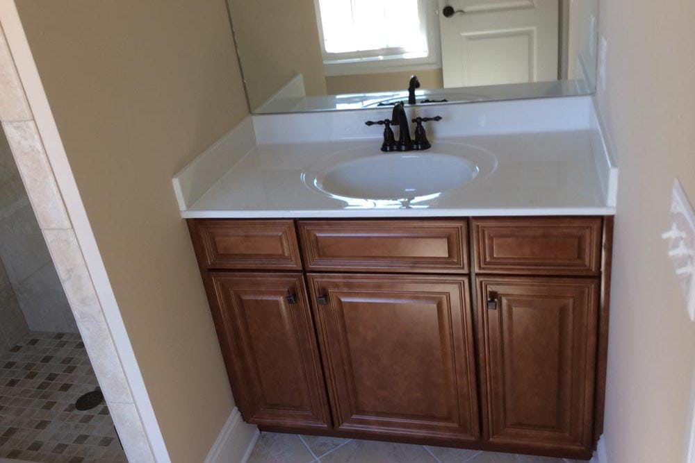 White countertop single sink with smaller shower in bathroom in Round Hill home