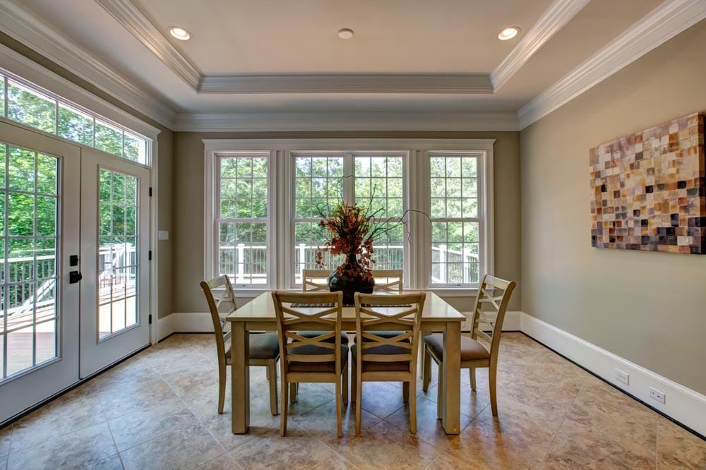 Windowed dining room next to glass paneled doors leading to deck