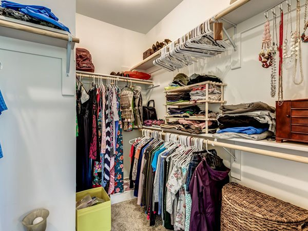 Master bedroom closet with clothes